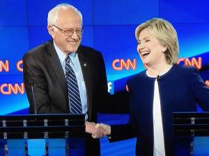 Bernie Sanders and Hillary Clinton shaking hands; Trent Vanegas