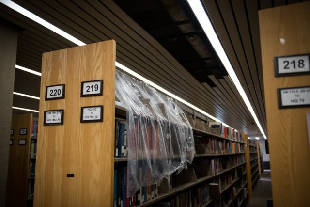 """Library shelves at Lehman College, part of the CUNY system, have been covered with plastic since a leak three years ago."" <-NYTimes caption"